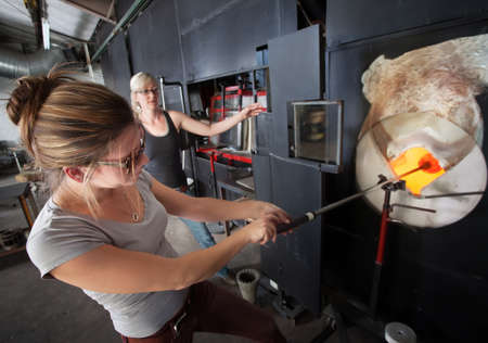 Two young glass artists working with hot furnace photo