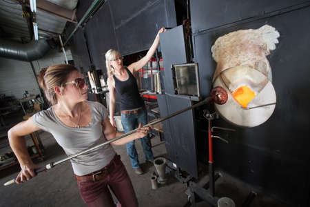 Two female glass artists working at a blast furnace photo