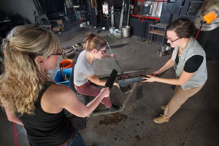 Trio of young white women working on glass art creation photo
