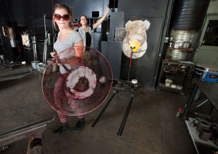 Serious industrial artist carrying hot plate jar with rod photo
