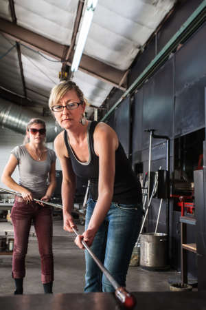 Blond glass artist working with molten glass object photo