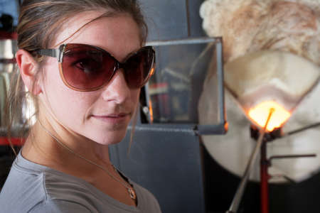 Cheerful female glass artisan near hot furnace photo