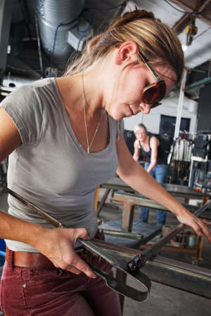 Pretty glass sculptor shaping tiny object on workbench photo