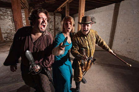 mace: Trio of threatening medieval characters charging with swords Stock Photo