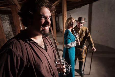 acting: Snarling Caucasian man with tough friends in medieval character Stock Photo