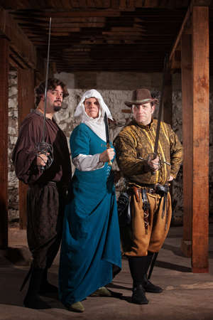 strong: Two renaissance knights with nun carrying weapons Stock Photo