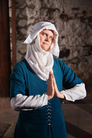 religious habit: Sinister middle ages nun in blue with hands together in prayer