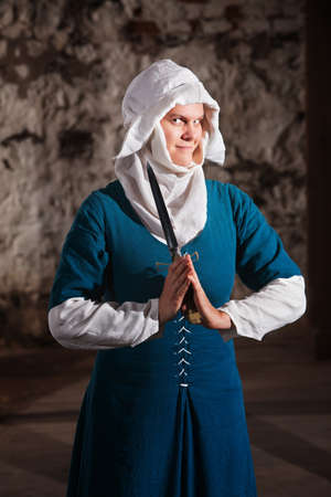 woman knife: Grinning nun in middle ages dress holding a dagger