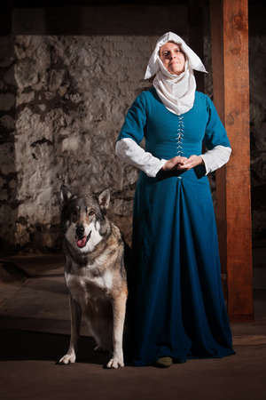 Peaceful medieval nun standing with pet dog Imagens