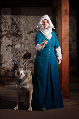 miffed: Insulted medieval nun pointing finger and standing with dog Stock Photo