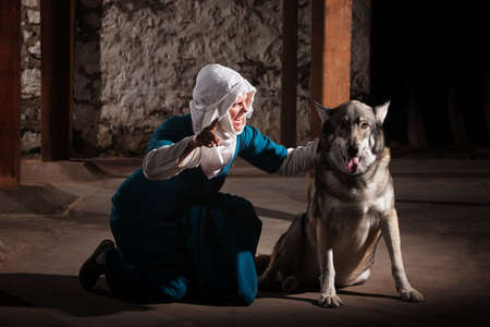 sic: Middle ages nun dog owner talking to her pet Stock Photo