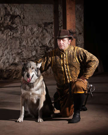 Serious mature medieval mercenary kneeling next to dog photo