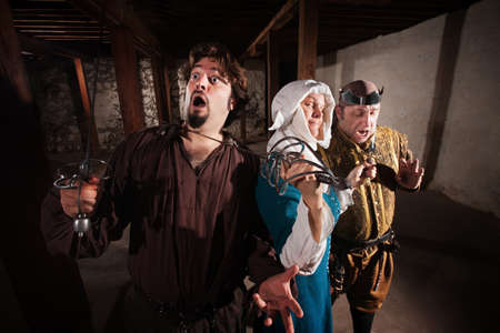 holding a knife: Brave middle ages nun with weapons on two men