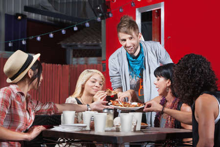 Smiling hipster serving pizza to group outside photo