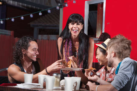 dining out: Mature woman with younger group eating pizza