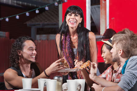 dining out: Joyful group of friends sharing pizza slices outdoors