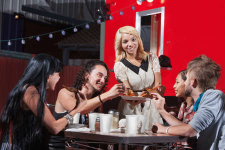 Young mixed woman sharing pizza with friends at cafe photo