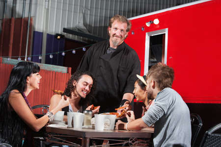 dining out: Smiling pizza canteen owner with happy customers