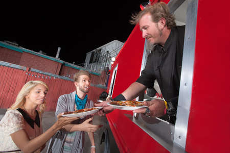 take out food: Chef serving carryout pizza from food truck