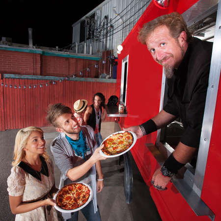 Food truck owner serving pizza to happy couple photo
