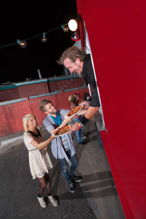 Happy teenagers served pizza from food truck owner photo