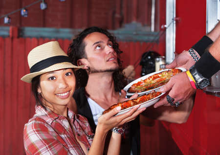 Cute Asian woman with carryout pizza from food truck photo