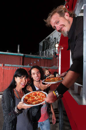 Smiling customers with food truck owner and pepperoni pizza photo