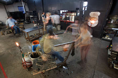 Busy workers moving in small business glass factory photo