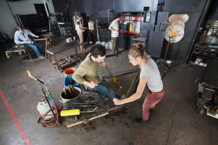 Two young glass artisans with tools in workshop photo