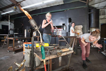 blowpipe: Distracted worker looking at co-worker from behind in glass factory
