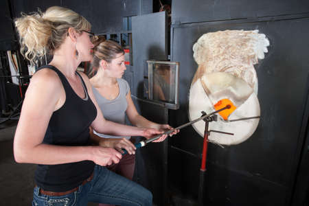 Young woman assisting glass art factory owner at kiln photo