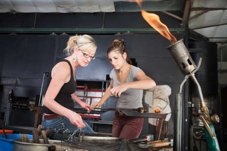 Worker helping woman clean iron tools at workbench photo