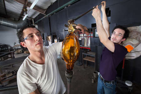 Pair of glass art students working together on piece photo