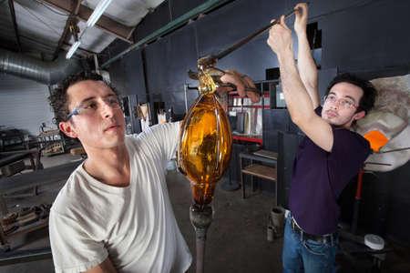 sudoracion: Un par de estudiantes de arte de vidrio trabajando juntos en la pieza