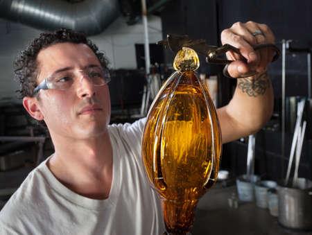 sculpting: Handsome European glass art student finishing vase