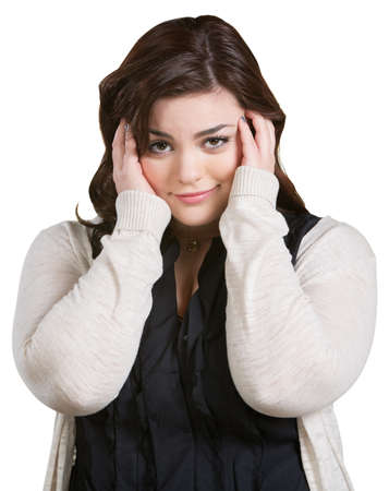 irked: Smirking young woman with hands on ears over white Stock Photo