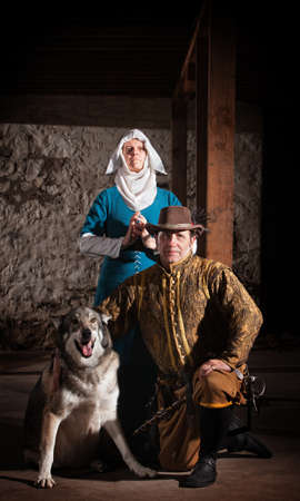 swashbuckler: Nun behind kneeling swashbuckler and dog in medieval character Stock Photo