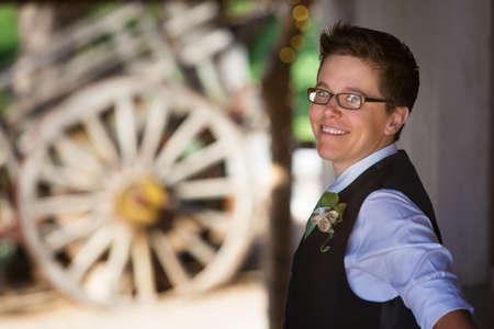 butch: Handsome lesbian groom outdoors in vest