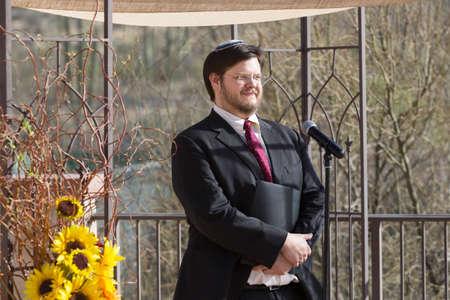 yarmulke: Smiling Caucasian Rabbi holding book by microphone Stock Photo