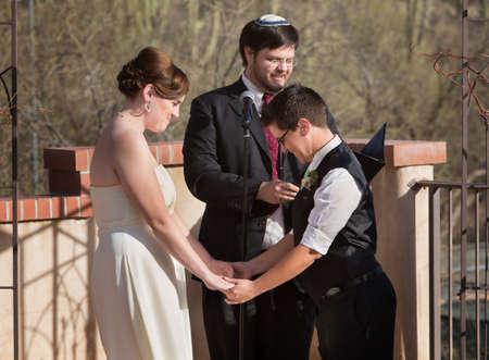 Homoseksueel paar hand in hand met rabbijn dienstdoende Stockfoto