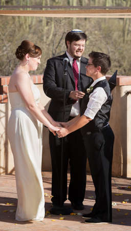 Couple standing and holding hands for wedding ceremony photo