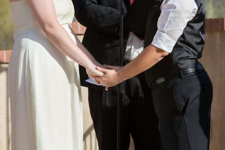 Women holding hands in wedding ceremony outdoors