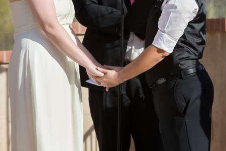 marriage ceremonies: Women holding hands in wedding ceremony outdoors