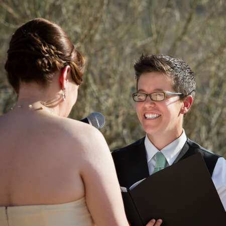 Happy lesbian lady reading vows to bride photo
