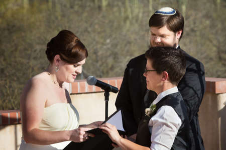 Lesbian white couple reciting marriage vows in ceremony photo