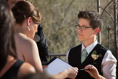 Lesbian partners reading marriage vows in ceremony photo