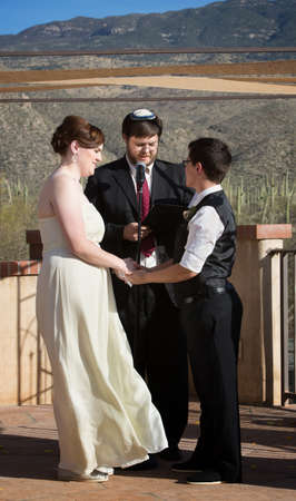 Rabbi blessing lesbian marriage ceremony in desert photo