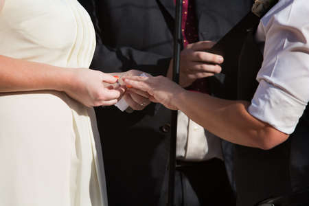 placing: Woman putting ring on finger of partner in civil union Stock Photo