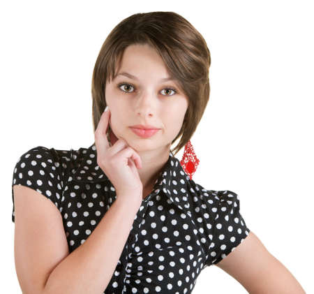 Serious European woman in polka dots with finger on cheeks photo
