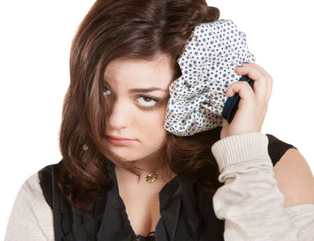 pathetic: Isolated brunette female with ice pack on head
